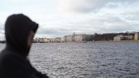 Unrecognizable man staying on city embankment. At winter sunny day stock video footage