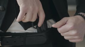Unrecognizable man in a suit shoves a gun by the belt of his pants close up. Criminal authority, mafia, criminal gang. Cool dangerous guy. The head of the stock video footage