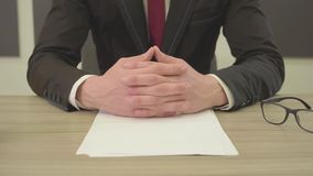 Unrecognizable man in the suit sitting at the table with crossed fingers in front of blank papers, pens and glasses. Big. Unrecognizable man in the suit sitting stock footage