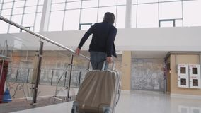 Unrecognizable man with suitcase hurrying. Businessman runing with laggage in airport terminal or train station. stock video
