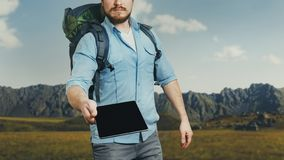 Unrecognizable man traveler with backpack holds a digital tablet stock photos