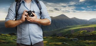 Unrecognizable Man Traveler Blogger Man With Backpack And Film Camera Near Mountains. Hiking Tourism Journey Concept. Unrecognizable Man Traveler Blogger Man Stock Photo