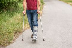 Walking exercises with crutches and an orthosis on the lower leg. An unrecognizable man walks on crutches after being operated on for a torn Achilles tendon; to stock photo