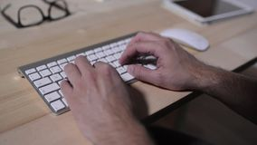 Unrecognizable man working from home, writing on computer keyboard stock footage