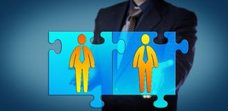Unrecognizable Manager Connects Two Professionals. Unrecognizable manager holding two connected jigsaw puzzle pieces with business man icons. Concept for Royalty Free Stock Images