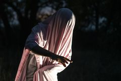 Unrecognizable maniacki morderstwo w białym pustym prześcieradle w noc lesie f fotografia royalty free