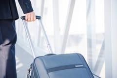 Unrecognizable Mann steht und hält Koffer an Stockfotografie