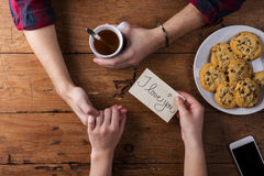 Unrecognizable mans and womans hands. Romantic message. Tea and cookies. Royalty Free Stock Photo