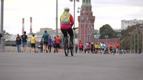 Unrecognizable marathon runners and cyclists against Moscow Kremlin. 4K background bokeh long shot stock video footage