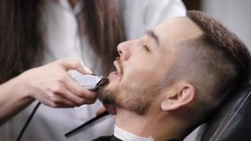 Unrecognizable master grooming beard of man with trimmer in barber shop stock video footage