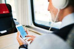 Mature businessman with smartphone travelling by train. Unrecognizable mature businessman travelling by train. A man with smartphone and headphones, listening Stock Image