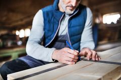 A man worker in the carpentry workshop, working with wood. An unrecognizable mature man worker in the carpentry workshop, working with wood royalty free stock photo