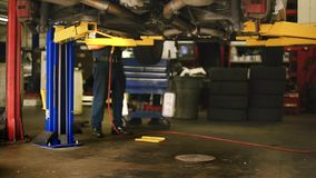 Unrecognizable Mechanic working under a Car. Shot from waist down of an unrecognizable mechanic working under a car at shop stock footage
