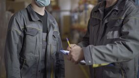 Unrecognizable men in face masks shaking hands after signing transportation documents. Caucasian male employees passing