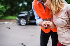 An unrecognizable man helping a young woman to walk after a car accident. Stock Image
