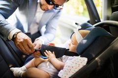 Unrecognizable man putting baby girl in the car. Unrecognizable men putting baby girl in the car. Father fastening seat belts Royalty Free Stock Photos