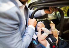 Unrecognizable man putting baby girl in the car. Unrecognizable men putting car seat with a baby girl in the car Royalty Free Stock Photography