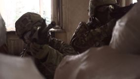 Unrecognizable modern soldiers taking cover behind a pile of sandbags. Clip stock footage