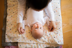 Unrecognizable mother holding hands of her cute baby son Royalty Free Stock Photo