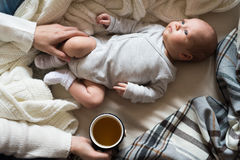 Unrecognizable mother with newborn baby son lying on bed Royalty Free Stock Photos