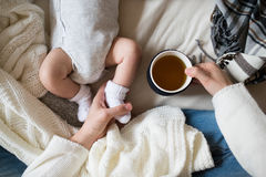 Unrecognizable mother with newborn baby son lying on bed Royalty Free Stock Image