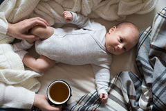 Unrecognizable mother with newborn baby son lying on bed Stock Photography