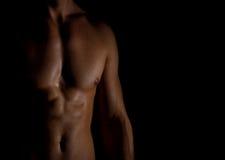 Unrecognizable muscular male body. Unrecognizable muscular male body on black background Royalty Free Stock Image