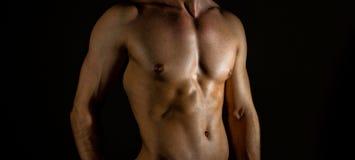 Unrecognizable muscular male body. Unrecognizable muscular male body on black background Stock Image