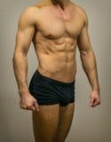 Unrecognizable muscular male body. Unrecognizable muscular male body on grey background Stock Photography