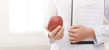 Unrecognizable nutritionist holding apple and diet plan in offic royalty free stock photo
