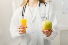 Unrecognizable nutritionist woman with fruit. Unrecognizable nutritionist woman with orange juice and apple at office, copy space. Healthy eating, right Royalty Free Stock Photo