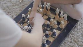 Unrecognizable ojciec i mała dziewczynka bawić się szachowego obsiadanie na podłodze na puszystym dywanie zamkniętym w górę Córek zbiory
