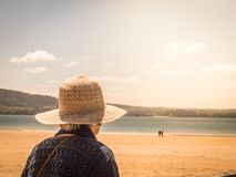 Unrecognizable old woman looking at a couple in a beach. Unrecognizable old woman with hat looking at a couple in a beach stock photography