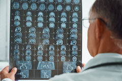 Unrecognizable older doctor examines MRI image Stock Photos
