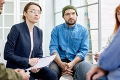 Opening up at Group Therapy Session. Unrecognizable patient opening up to highly professional psychiatrist during group therapy session at cozy office stock image