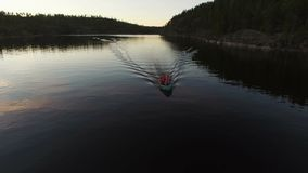 Unrecognizable people in boat at evening aerial. Shot stock video footage