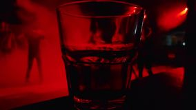 Unrecognizable people dance on background of a glass with an alcoholic beverage stock video footage