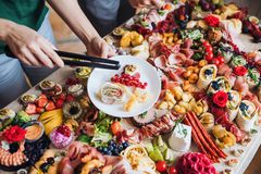 Unrecognizable people putting food on plates on a indoor family birthday party. A top view of unrecognizable people putting food on plates on a indoor family royalty free stock photo