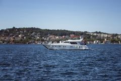 Unrecognizable people ride luxury white yacht. On Bosphorus in a sunny summer day in Istanbul. European side is in the background stock images