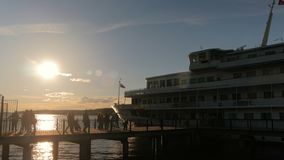 People silhouettes walking on pier. Unrecognizable people silhouettes returns to cruise ship. Sunset light, golden hour. Travelling concept stock video footage