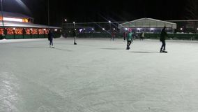 Unrecognizable people skate on ice rink at winter night stock video footage