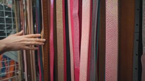 Unrecognizable person chooses a eco-leather belt in a store. Close-up of a hand that touches multicolored waist-belts hung in a self-service store. Woman stock video footage