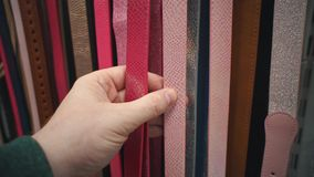 Unrecognizable person chooses a eco-leather belt in a store. Close-up of a hand that touches multicolored waist-belts hung in a self-service store. Man chooses stock video