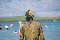 Unrecognizable person in healthy mud on beach Royalty Free Stock Photography
