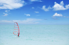 Unrecognizable person practicing windsurf. On sea and blue sky stock images