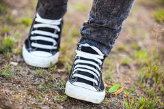 Unrecognizable person in rubber shoes walks on footpath, front view Royalty Free Stock Photo