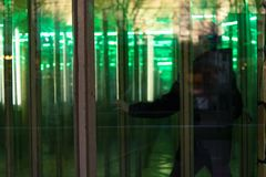 Unrecognizable person seeking the way out in a house of mirrors, a glass maze on an amusement funfair, copy space. Selected focus royalty free stock photo