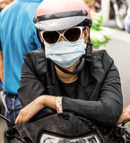 Unrecognizable Person with a Smog Face Mask. Frontal view of an absolutely unrecognizable person with a smog face mask sitting on a scooter Royalty Free Stock Photography