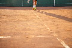 Person walking along the line of a ground tennis court. Unrecognizable person walking along the line of a ground tennis court on a sunny day Stock Images