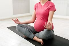 Unrecognizable pregnant woman meditating at home. Practicing yoga. Calm, relaxation, healthy pregnancy concept, copy space stock images